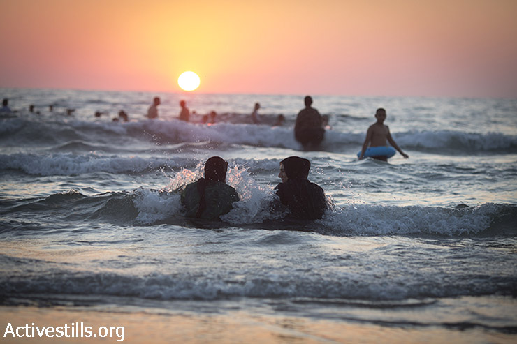 Donne Palestinesi si godono il mare mediterraneo durante le vacanze dell' Eid al-Fitr al tramonto a Giaffa, July 18, 2015. Israeli authorities issued thousands of permits for Palestinians living in the West Bank, allowing them to visit Israel during the three-day holiday that marks the end of the holy fasting month of Ramadan